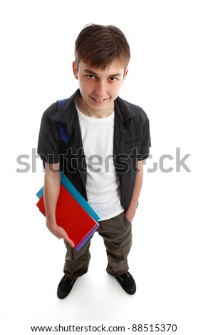A male teenage student standing in casual clothes and holding some books in one hand.  White background.