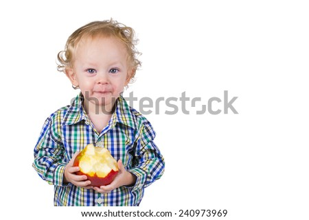 A male toddler holds an apple and looks into the camera. Isolated on white. - stock photo
