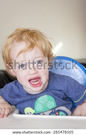 A male toddler sat in a highchair crying - stock photo