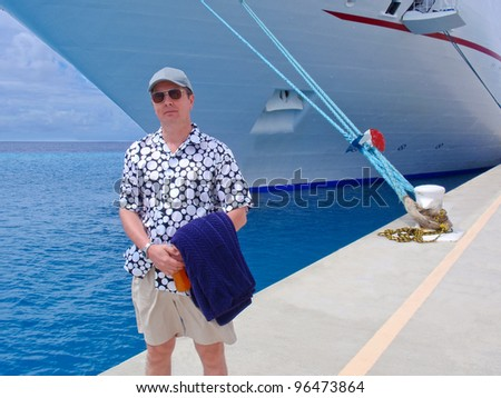 A male tourist over the passenger ship in port. - stock photo