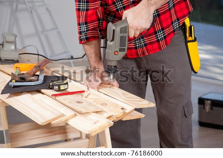 A male using an electric hand drill on a plank - stock photo