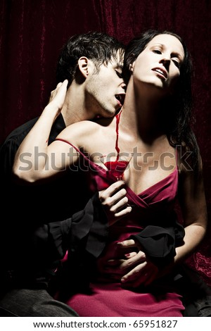 A male Vampire is sucking the blood of his female prey and holding a glass below, where the spilled blood is flowing down. - stock photo