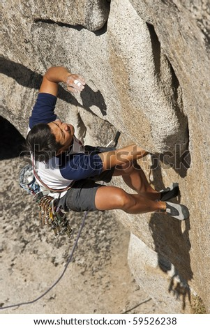 A male, Vietnamese rock climber grips a steep overhang on a sunny day. - stock photo