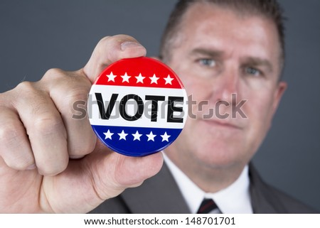 A male voter holds up a vote pin to promote democratic elections in the United States - stock photo