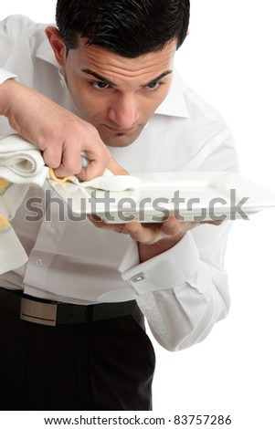 A male waiter servant or other hospitality staff worker is cleaning and polishing a white plate ready for service. - stock photo