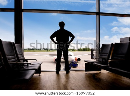 A male waits in a terminal at an airport - stock photo