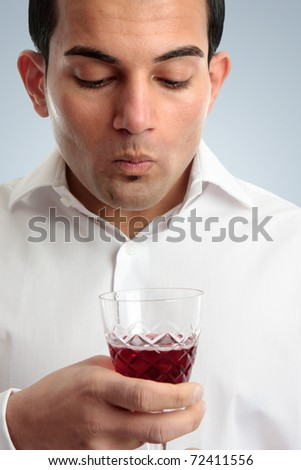 A male wine taster savours a wine by swirling and holding it in the mouth for a few seconds to saturate the taste buds. - stock photo