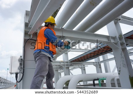 A male worker doing a maintenance work by cleaning and inspecting explosion proof security camera.