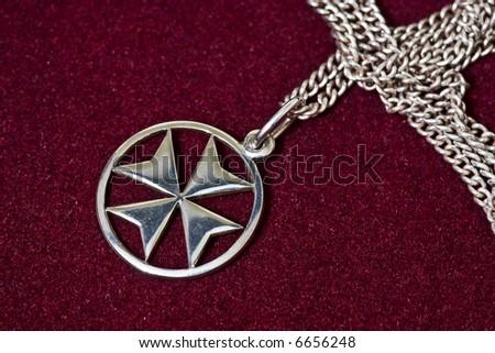 A Maltese cross silver pendant on velvet background. - stock photo