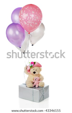 """A mama and baby bear on a silver-wrapped gift holding colorful balloons, one of which says, """"It's a girl"""".  Isolated on white. - stock photo"""