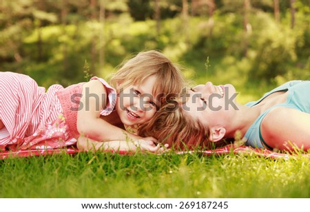 a Mama and her little daughter lie on the grass  - stock photo