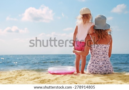 a Mama and her little daughter playing on the beach - stock photo