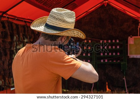 A man aims a weapon at a target - stock photo