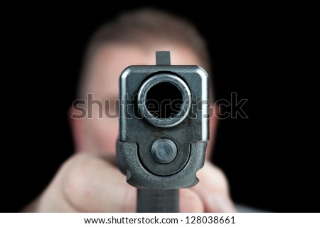 A man aims his semi automatic pistol. Selectively focused on the front of the gun. - stock photo