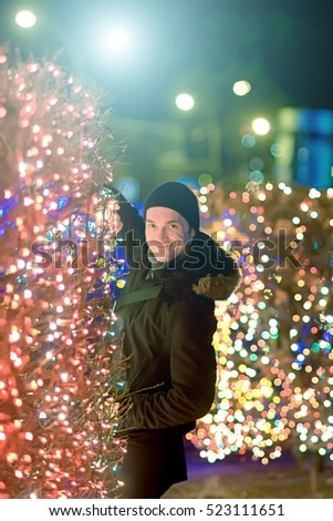 A man among the bright colored Christmas lights garlands.