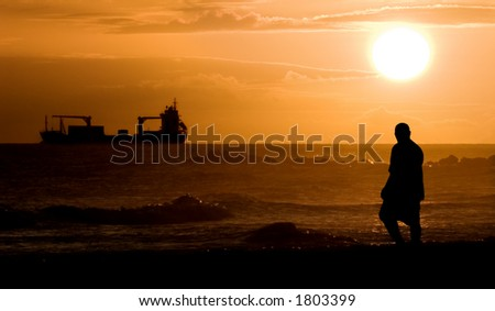 A man and a freighter are silhouetted before a beautiful Barbadian sunset. - stock photo