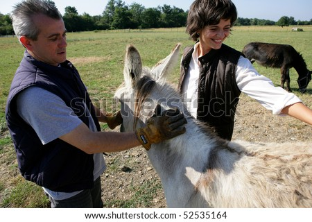 A man and a smiling woman with a donkey