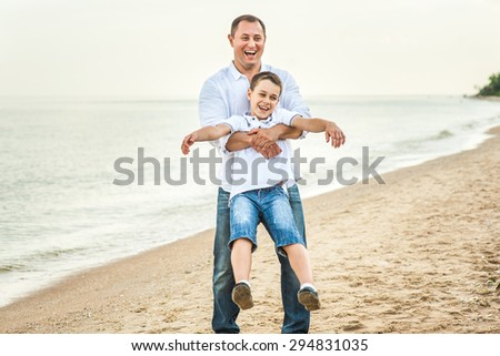 A man and a teenage boy playing on the beach with a friendly attitude