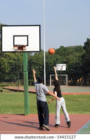 A man and a woman are playing on a park basketball court.  They are looking at and chasing after a basketball in the air.  Vertically framed shot. - stock photo