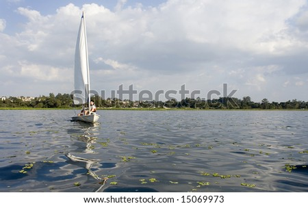 A man and a woman are sailing a sailboat on a lake.  Horizontally framed shot. - stock photo