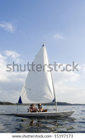 A man and a woman are sailing a sailboat on a lake.  Vertically framed shot. - stock photo