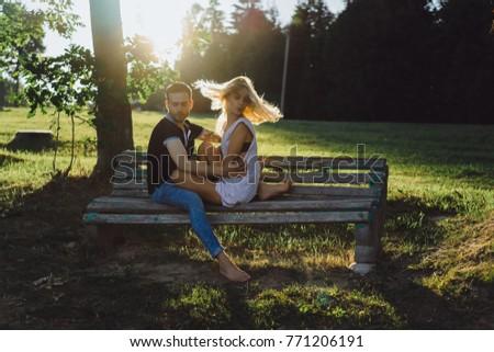 man woman sitting on bench kissing stock photo royalty free