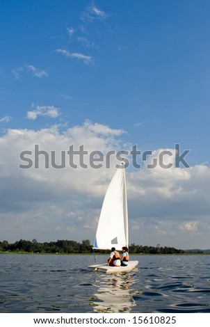 A man and a woman are sitting together on a sailboat.  Vertically framed shot. - stock photo