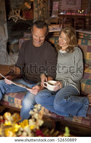 A man and a woman are smiling and sitting on a couch reading a newspaper. The woman is holding a coffee cup. Vertical shot. - stock photo