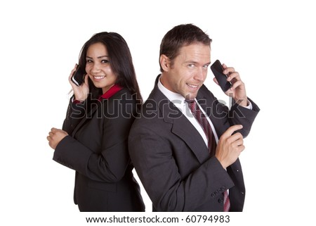 A man and a woman are standing back to back talking on there phones.  Both have a happy expression on there face. - stock photo
