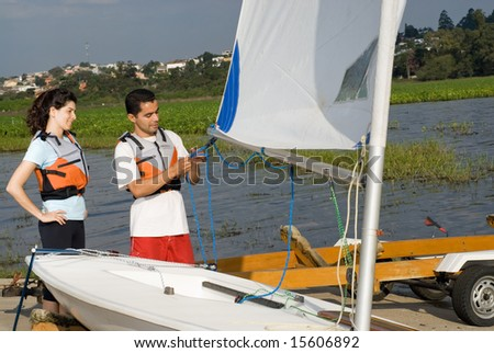 A man and a woman are standing next to a sailboat on a lake. The man is tying a knot.  They are looking away from the camera.  Horizontally framed shot. - stock photo