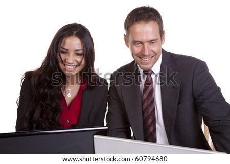 A man and a woman are working on laptop computers and smiling. - stock photo