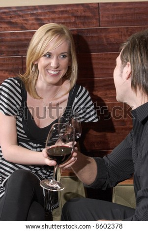A man and a woman conversate at a wine lounge