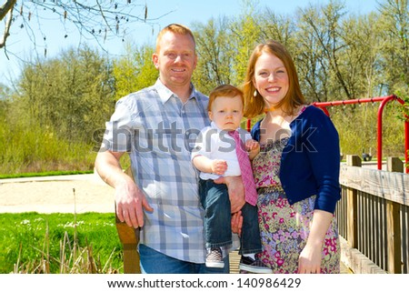 A man and a woman hold their baby one year old son while posing for a family photo outdoors.
