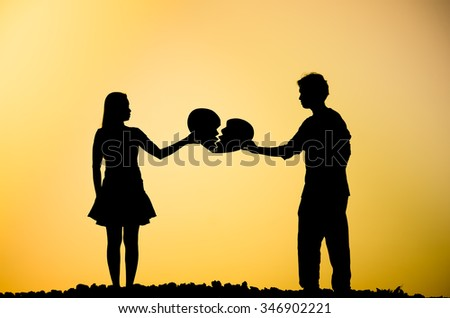 A man and a woman holding a broken heart - stock photo