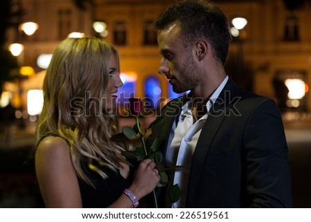 A man and a woman holding a rose looking at each other with love - stock photo