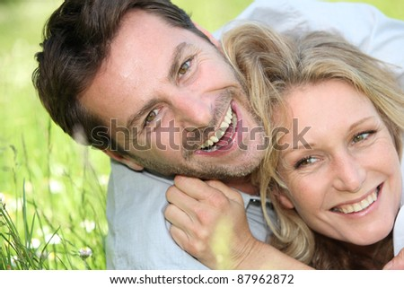 A man and a woman holding each other and laughing on the grass.