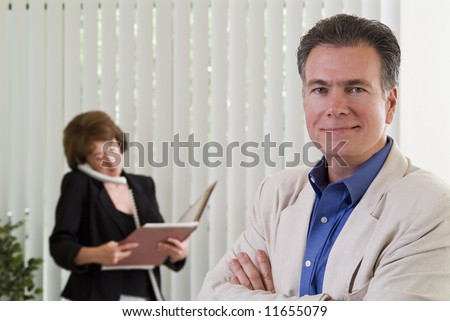 A man and a woman in a business setting with the man in focus in the foreground. - stock photo