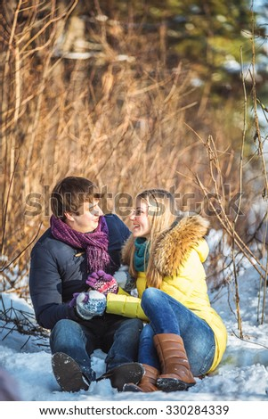 A man and a woman in a winter park. Ski resort. Loving couple sitting in the snow, smiling. Sunny day. Couple dressed in warm jackets and mittens. - stock photo