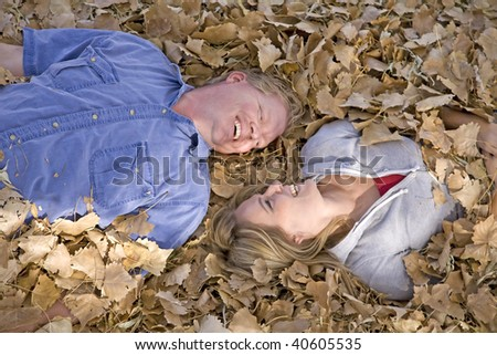A man and a woman laying in the fall leaves laughing and looking at eachother.