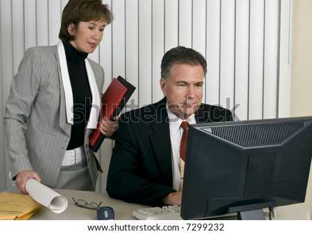 A man and a woman looking at a computer screen with pleased expressions on their faces. - stock photo