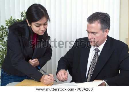 A man and a woman looking at a document that the woman is about to sign. - stock photo