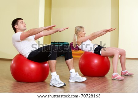 A man and a woman making exercises on balls - stock photo