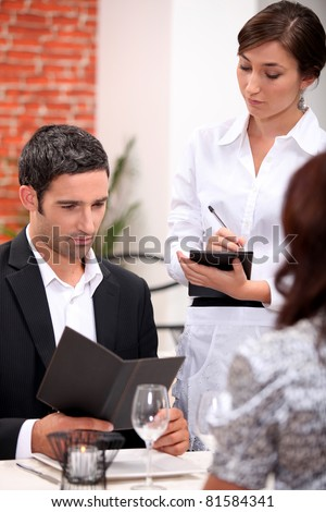 a man and a woman ordering at the restaurant, a waitress is writing the order