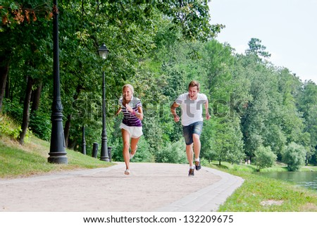 a man and a woman running in the park race - stock photo