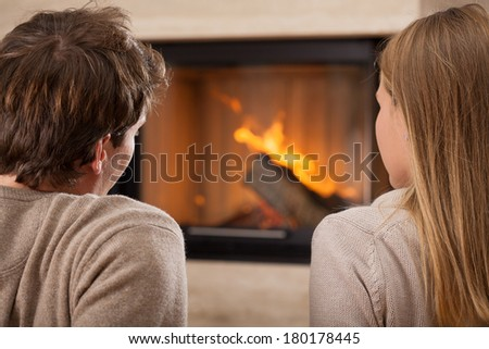 A man and a woman sitting by a fireplace