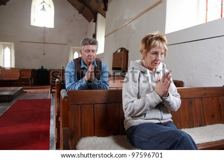 A man and a woman sitting in a church praying - stock photo
