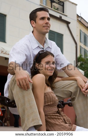 A man and a woman sitting on stairs - stock photo