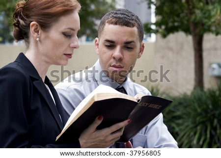 A man and a woman who are sitting together reading from the Holy Bible, perhaps while on break from work. - stock photo