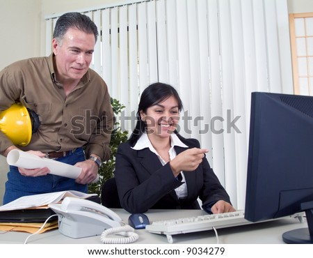 A man and a young woman amused at what they see on the computer monitor.