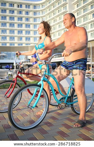 A man and a young woman in bathing suits on bikes on the hotel in the evening - stock photo
